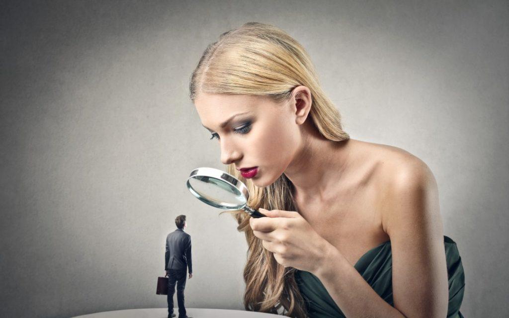 Mujer mirando hombre con lupa